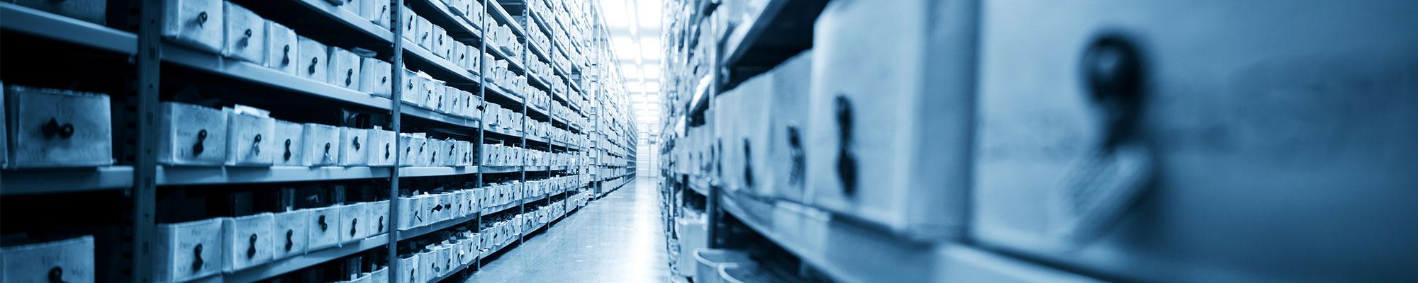 Archiv mit langen Regalen die gefüllt sind mit Akten und Ordnern