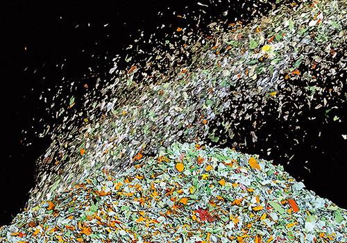 Ein Haufen mit farbigen Papierschnipseln auf den weitere Papierschnipsel geblasen werden