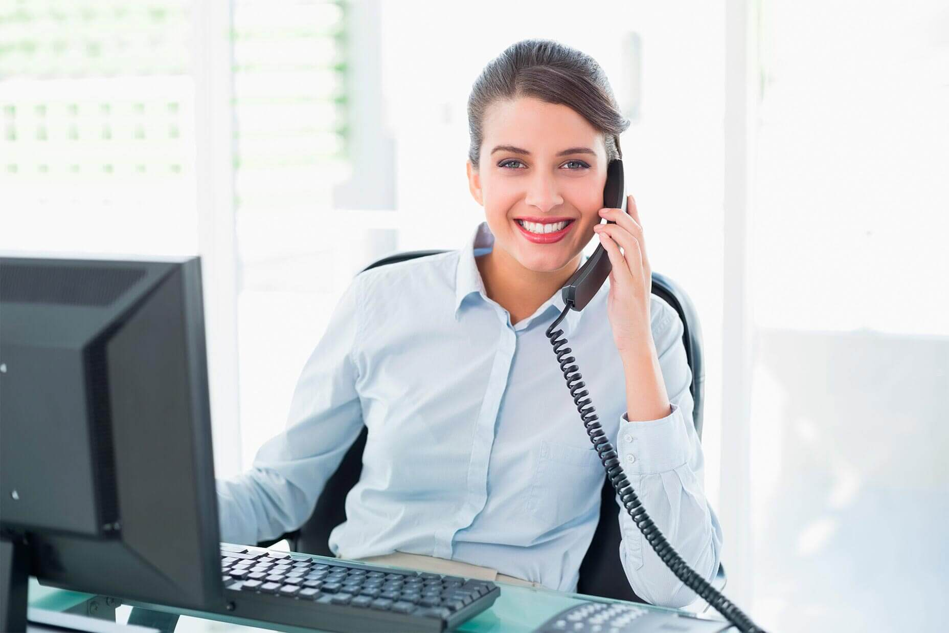 Junge, weibliche Reisswolf angestellte hält den Telefonhörer in der Hand und lächelt in die Kamera