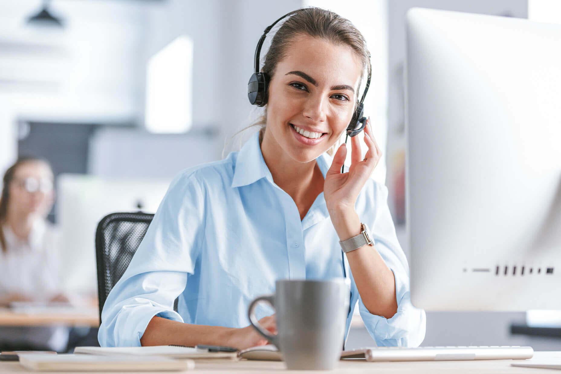 Junge weibliche Reisswolf-Angestellte mit Headset lächelt in die Kamera