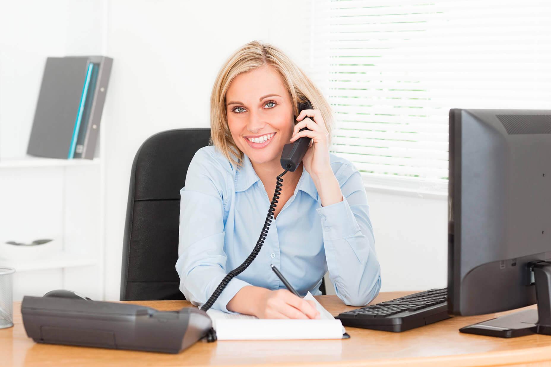 Junge weibliche Reisswolf Angestellte hält Telefonhörer in der Hand und lächelt in die Kamera