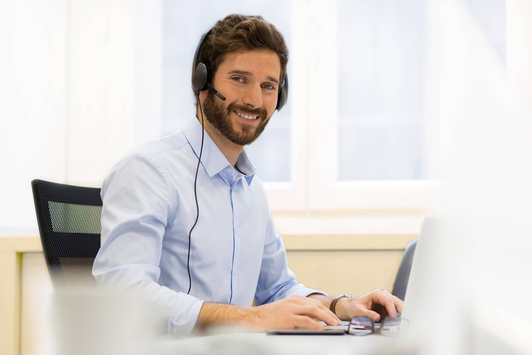 Junger männlicher Angestellter vpn Reisswolf mit Headset lächelt in die Kamera